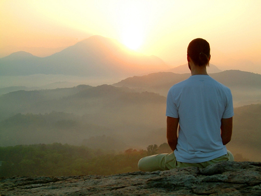 man meditating at mountain sunrise