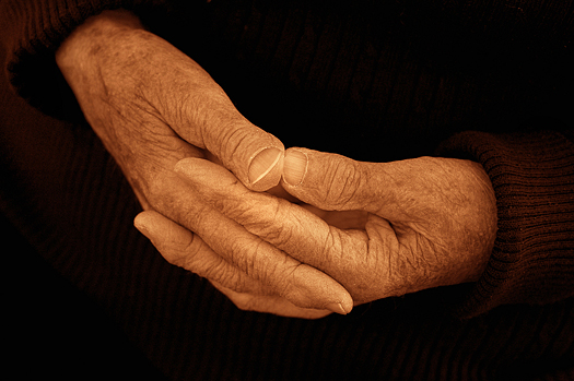 The calm composed hands of an 80 year old woman. Black and white sepia toned.