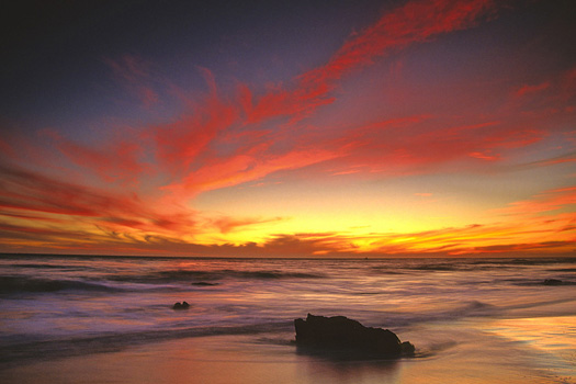 brooding beach sunset in red and yellow at el matador beach near malibu california usa north america