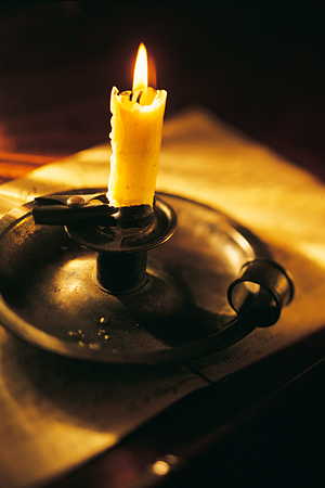 A lit candle in a holder on a table