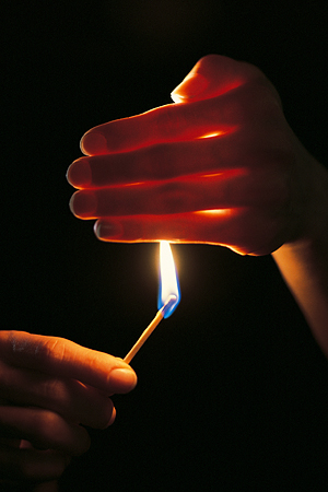 A lit match being shielded by a human hand