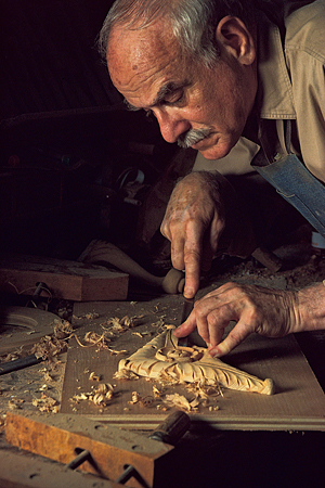 A woodworking man concentrating on an intricate piece of carving
