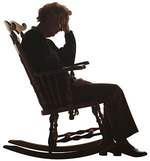 Silhouette of a sad elderly woman in a rocking chair