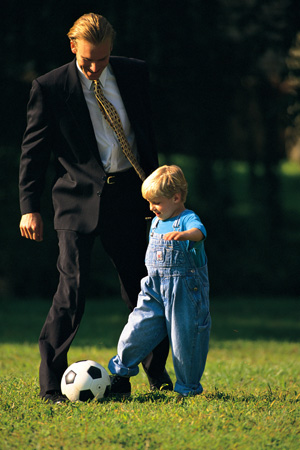 Father and son kicking soccer ball on lawn
