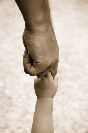 Holding Hands. An adult hand holds a child's hand