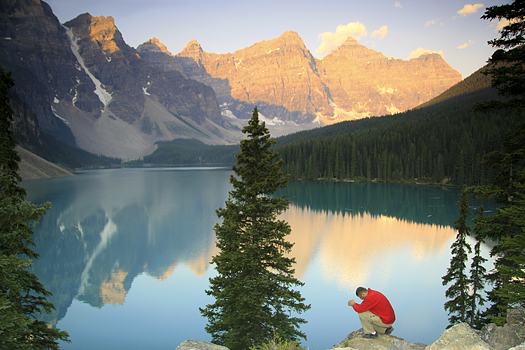 Majestic mountains reflected in lake, with single man kneeling in prayer in forefront