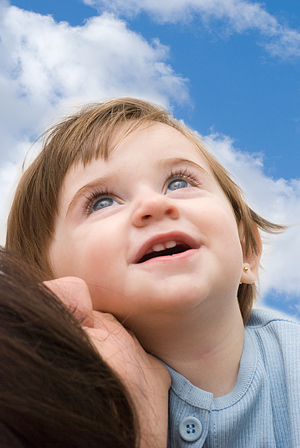 Smiling girl with mother looking upwards.