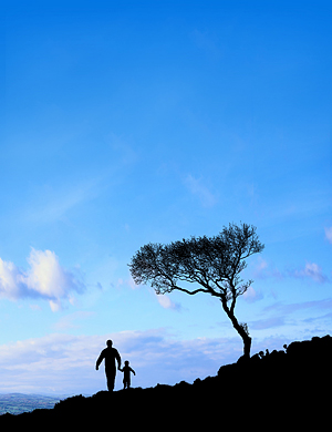 Silhouette of father and son on the foreground with the sky on background.