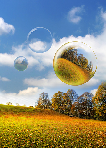 Three Bubbles float across a leaf covered Park on a stunning Bright Autumnal Day in Northumberland England