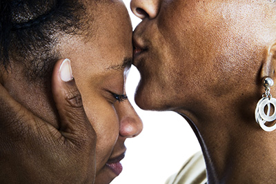 mother kissing daughter's forehead